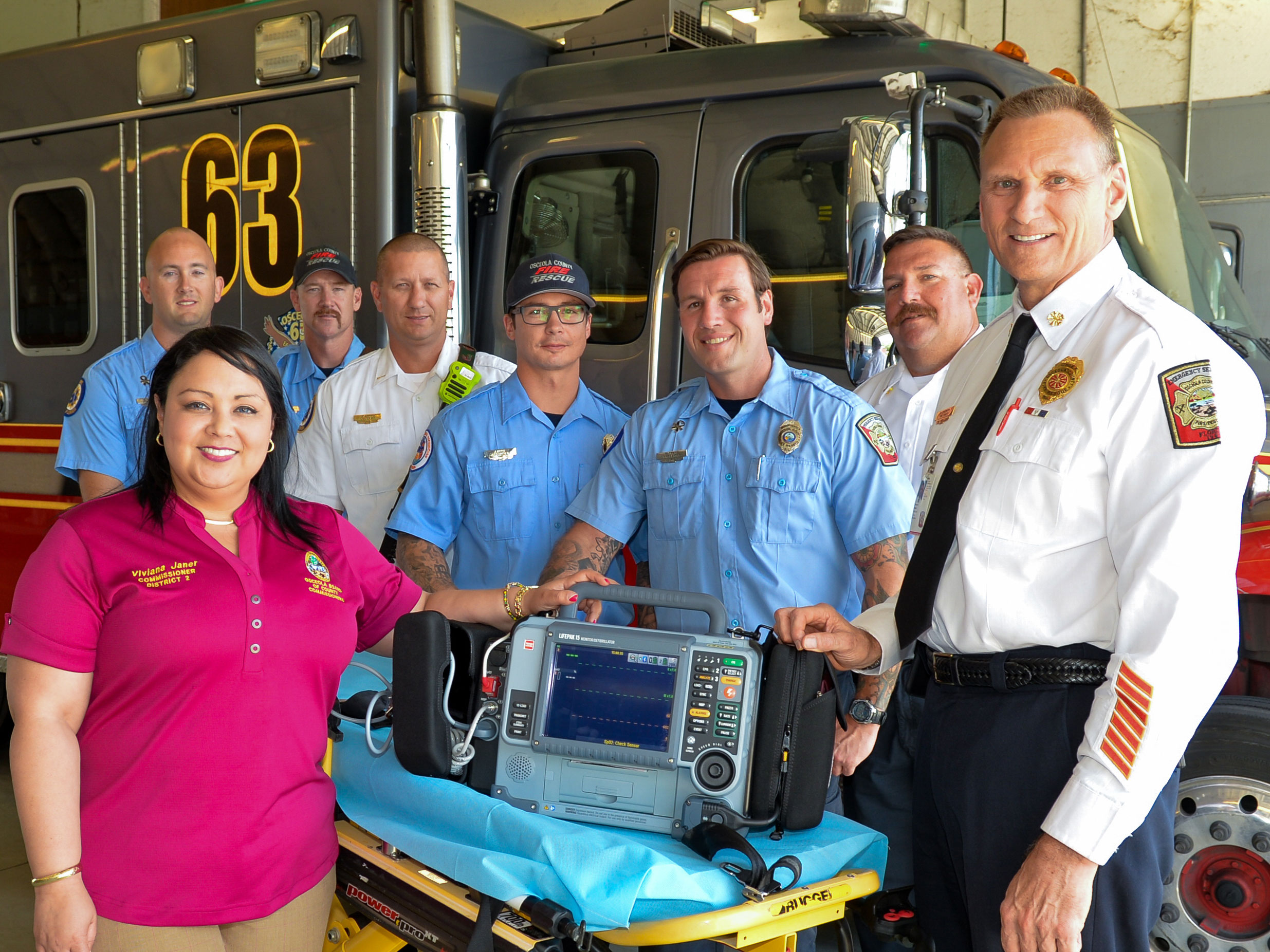 Osceola Commission Chairwoman Viviana Janer, left, with Fire Chief Robert Sorenson, far right, and members of Station 63 with the new LIFEPAK 15.
