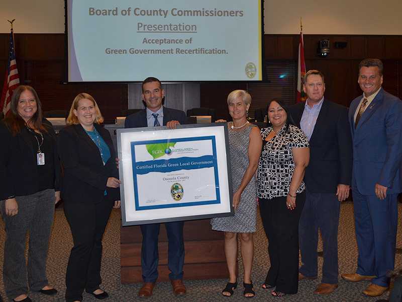 Osceola County Commissioners and County staff receive a framed copy of the Florida Green Government certificate from representatives of the Florida Green Building Coalition during the Monday, August 6 meeting of the BOCC.